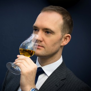 A man, smelling a glass of whisky
